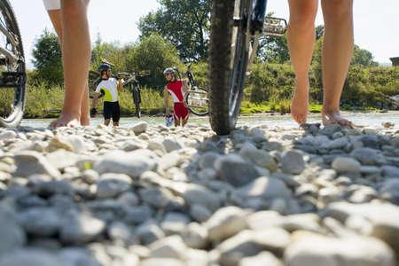 ciclos: Amigos caminando sobre piedras con sus ciclos