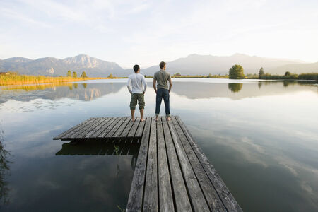 men standing: Two men standing on a pier LANG_EVOIMAGES