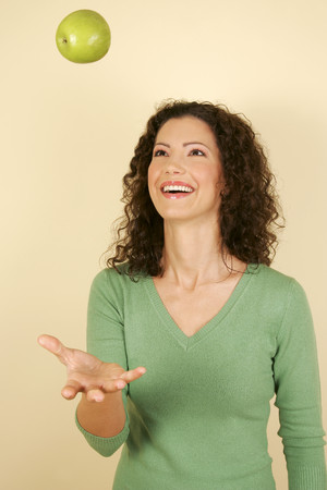 A woman throwing an apple in the air Stock Photo