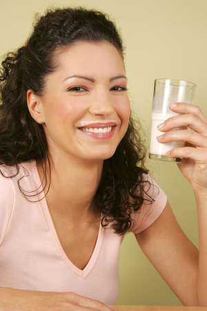 A woman holding a glass of milk