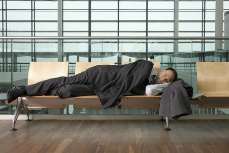 lag: A businessman asleep in airport lounge LANG_EVOIMAGES