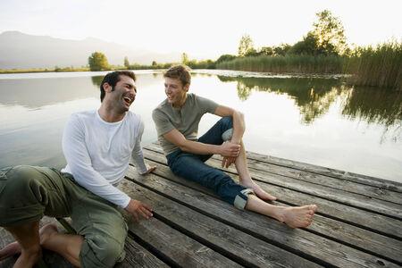dos personas conversando: Dos amigos que se relajan en el muelle