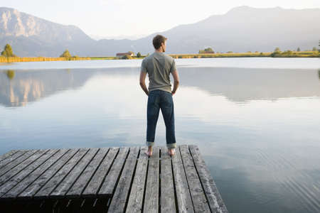 alpine water: A man standing on a pier LANG_EVOIMAGES