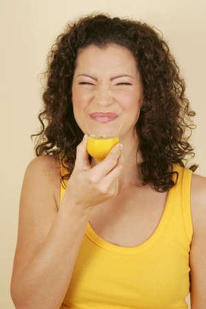 A woman making a face while having a lemon