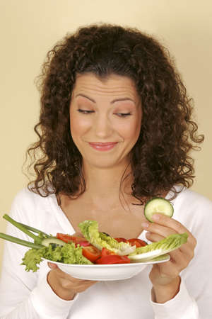 A woman holding a plate of salad
