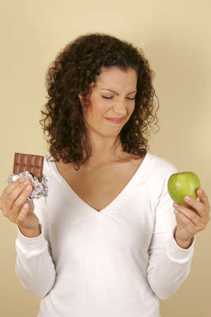 A woman holding a chocolate and an apple
