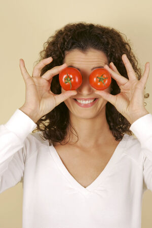 A woman covering her eyes with tomatoes Stock Photo