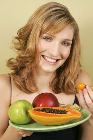 spaghetti strap: A woman holding a plate of fruits