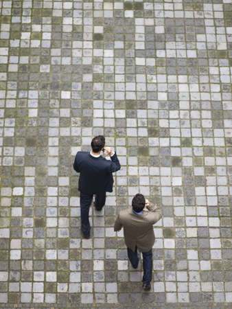 two persons only: Two businessmen walking across a place and talking on the cellphone