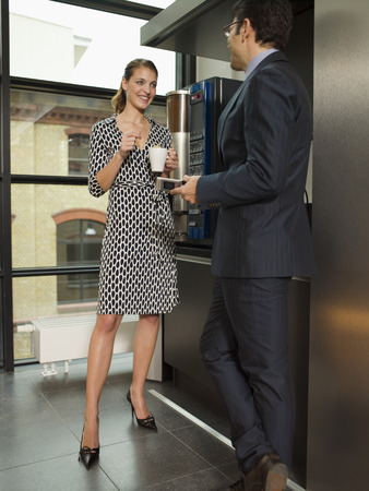 Two office people talking by the coffee maker Stock Photo