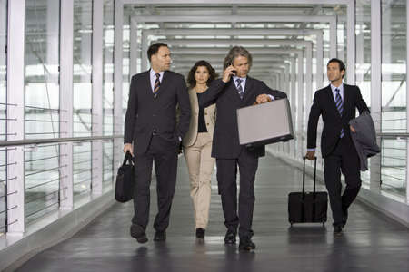 business people walking: Four business people at the airport