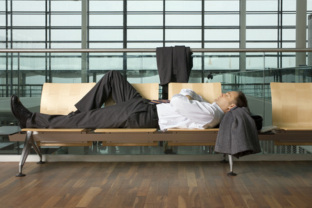 man in chair: A businessman asleep in airport lounge LANG_EVOIMAGES