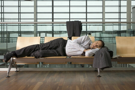 airport lounge: A businessman asleep in airport lounge LANG_EVOIMAGES