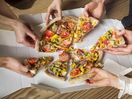 Menschen greifen Pizza LANG_EVOIMAGES
