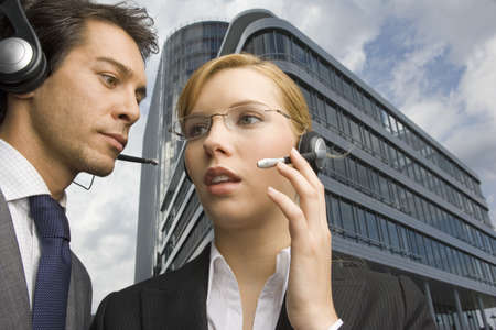 low blouse: Two business people wearing headsets