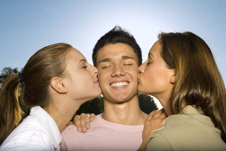 spiked hair: Two teenage girls kissing a boy LANG_EVOIMAGES