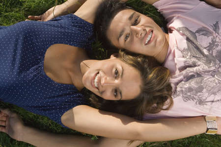 girl short hair: A teenage couple lying down on the grass