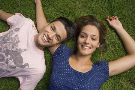 spiked hair: A teenage couple lying down on the grass