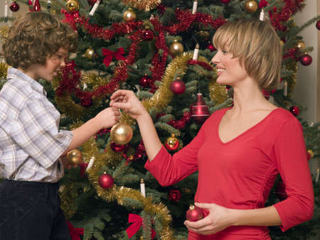 decorating christmas tree: Mother and son decorating Christmas tree LANG_EVOIMAGES