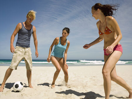 two piece swimsuit: People playing football on the beach LANG_EVOIMAGES