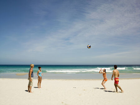 beach blond hair: Friends playing volleyball on the beach