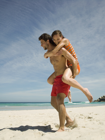 carrying girlfriend: Man carrying girlfriend on back