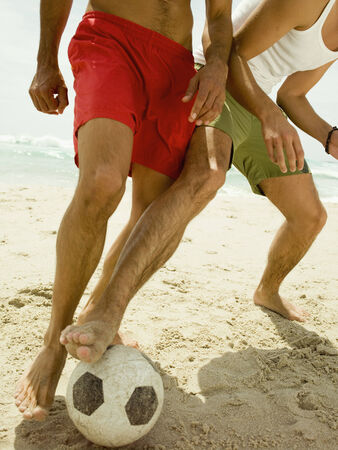 two persons only: Men playing football on the beach LANG_EVOIMAGES