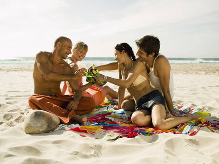 two piece swimsuit: Friends drinking beer on the beach LANG_EVOIMAGES