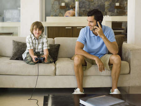 checkered polo shirt: Boy playing playstation,father on the phone LANG_EVOIMAGES