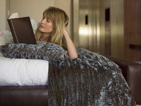 mujer leyendo libro: Una mujer lee un libro LANG_EVOIMAGES