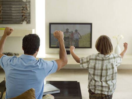 checkered polo shirt: Father and son watching TV