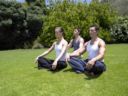 young men: Young woman and two young men meditating on a lawn