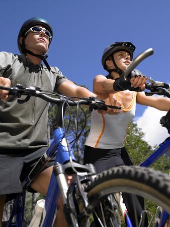 mountain biking: Low angle view of a young couple mountain biking