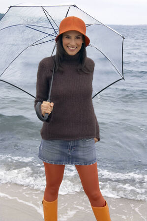 mini umbrella: Portrait of a young woman holding an umbrella on the beach LANG_EVOIMAGES