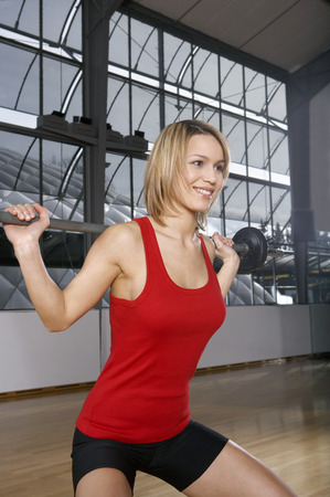 Woman doing weight training in gym Stock Photo