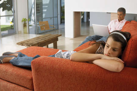 girl lying down: Muchacha que se acuesta en un sof�, el padre trabaja en la computadora port�til