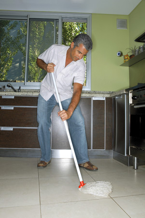 tidiness: Man mopping the kitchen floor
