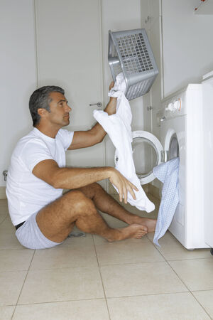 tidiness: Man putting clothes in the washing machine LANG_EVOIMAGES