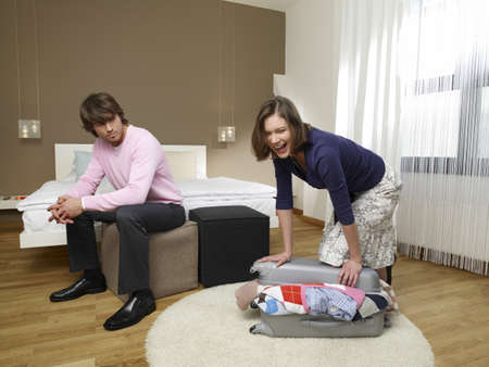 shutting: Man looking at his girlfriend shutting a suitcase
