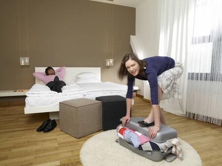 shutting: Man lying down as his girlfriend shutting a suitcase