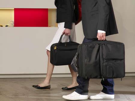 accomodation: Couple carrying their luggage in a hotel