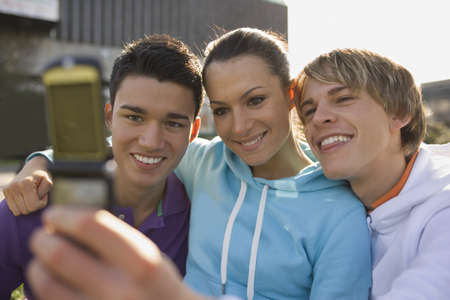 young men: A young woman and two young men looking at a mobile phone and smiling LANG_EVOIMAGES