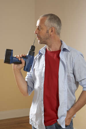 fully unbuttoned: Close-up of a mid adult man holding a drill