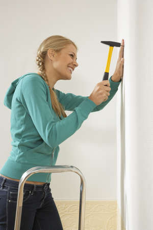 hammering: Side profile of a young woman hammering a nail into a wall