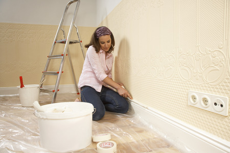 Young woman putting adhesive tape on a wall