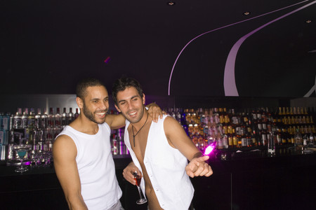 young men: Two young men standing in a nightclub and smiling LANG_EVOIMAGES