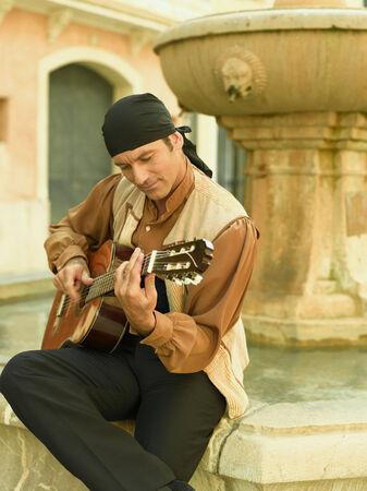 mid adult man: Hombre de mediana edad tocando la guitarra y mirando hacia abajo