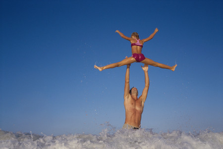 Mid adult man picking up his daughter in the sea