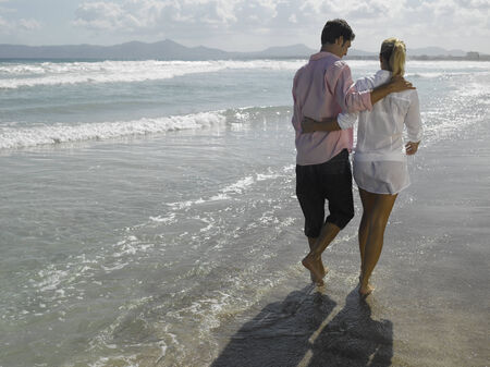 A mid adult couple walking on the beach