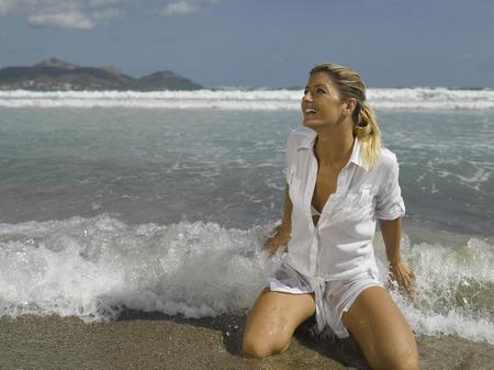 donna in ginocchio: Met� degli adulti donna in ginocchio sulla spiaggia LANG_EVOIMAGES